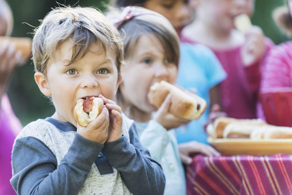 """<p>Hot dogs and other processed meat are not the ideal option for kids. In 2009, a study by the <a href=""""https://www.wcrf.org/dietandcancer/limit-red-and-processed-meat/"""" rel=""""nofollow noopener"""" target=""""_blank"""" data-ylk=""""slk:World Cancer Research Fund"""" class=""""link rapid-noclick-resp"""">World Cancer Research Fund</a> found that hot dogs, ham, bacon, salami, and other processed meats have no place in a healthy diet for children because of the sugar, fat, and salt contents. They say these can increase cancer risks.</p><p>Hot dogs can be dangerous in other ways too. According to <a href=""""https://www.hopkinsmedicine.org/health/wellness-and-prevention/a-dangerously-tasty-treat-the-hot-dog-is-a-choking-hazard"""" rel=""""nofollow noopener"""" target=""""_blank"""" data-ylk=""""slk:Johns Hopkins Medicine"""" class=""""link rapid-noclick-resp"""">Johns Hopkins Medicine</a>, research shows that hot dogs are the top cause of food-related choking in children under 3. This is because the BBQ favorite is the right size and consistency to block a child's airways. </p>"""