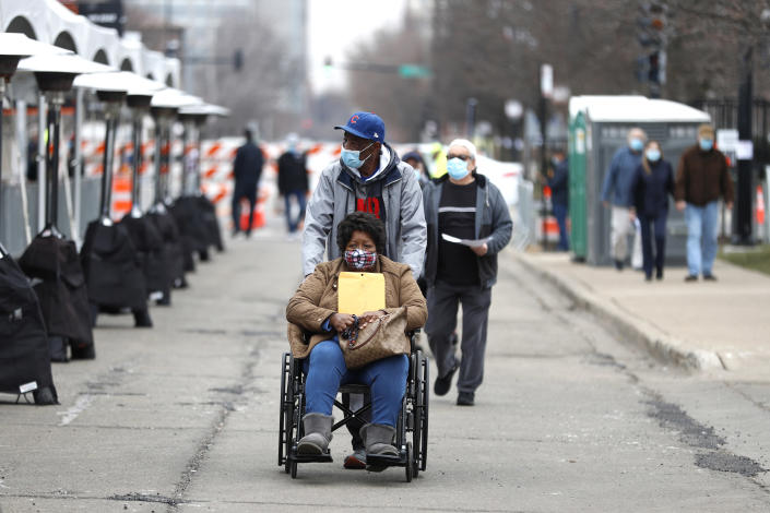 A woman in a wheelchair exits the United Center mass COVID-19 vaccination site on Wednesday, Feb. 10, 2021, in Chicago. The site will administer 6,000 shots per day at full capacity and will remain open seven days a week for eight weeks. (AP Photo/Shafkat Anowar)