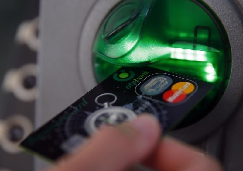 A customer performs a transaction on an ATM at a branch of Hungary's largest lender OTP Bank in central Budapest