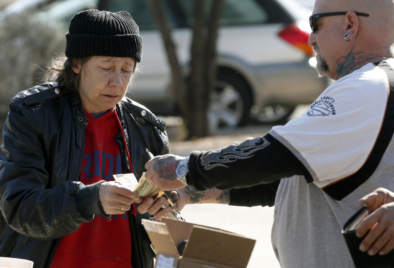 An impromptu gun buyer sells a gun to a woman that he purchased outside a police station in Tucson, Ariz. Tuesday, Jan 8, 2013. About a dozen buyers offered cash to sellers in the parking lot of a police station where Tucson City Councilman Steve Kozachik set up a gun buy back program asking people to turn in their guns for a $50 gift certificate to a grocery store. The buyers were trying to purchase weapons from sellers in an effort to circumvent Councilman Kozachik's buyback program. (AP Photo/Matt York)