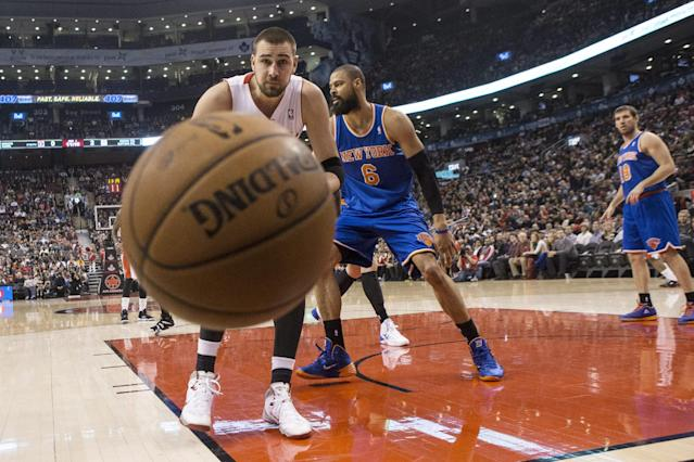 Toronto Raptors' Jonas Valanciunas, left, watches the ball go out of play after a tussle with New York Knicks' Tyson Chandler, center, during first-half NBA basketball game action in Toronto, Saturday, Dec. 28, 2013. (AP Photo/The Canadian Press, Chris Young)