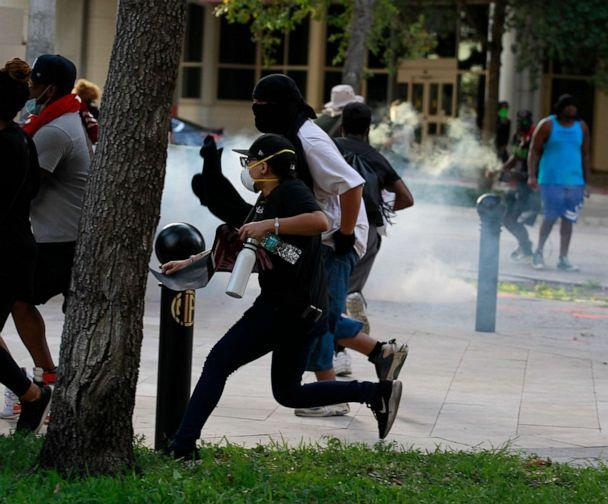 PHOTO: Protesters scatter as Fort Lauderdale police shoot tear gas at them near the municipal garage in downtown Fort Lauderdale near Wayne Huizenga Park on May 31, 2020. (Carl Juste/Miami Herald/Tribune News Service via Getty Images)