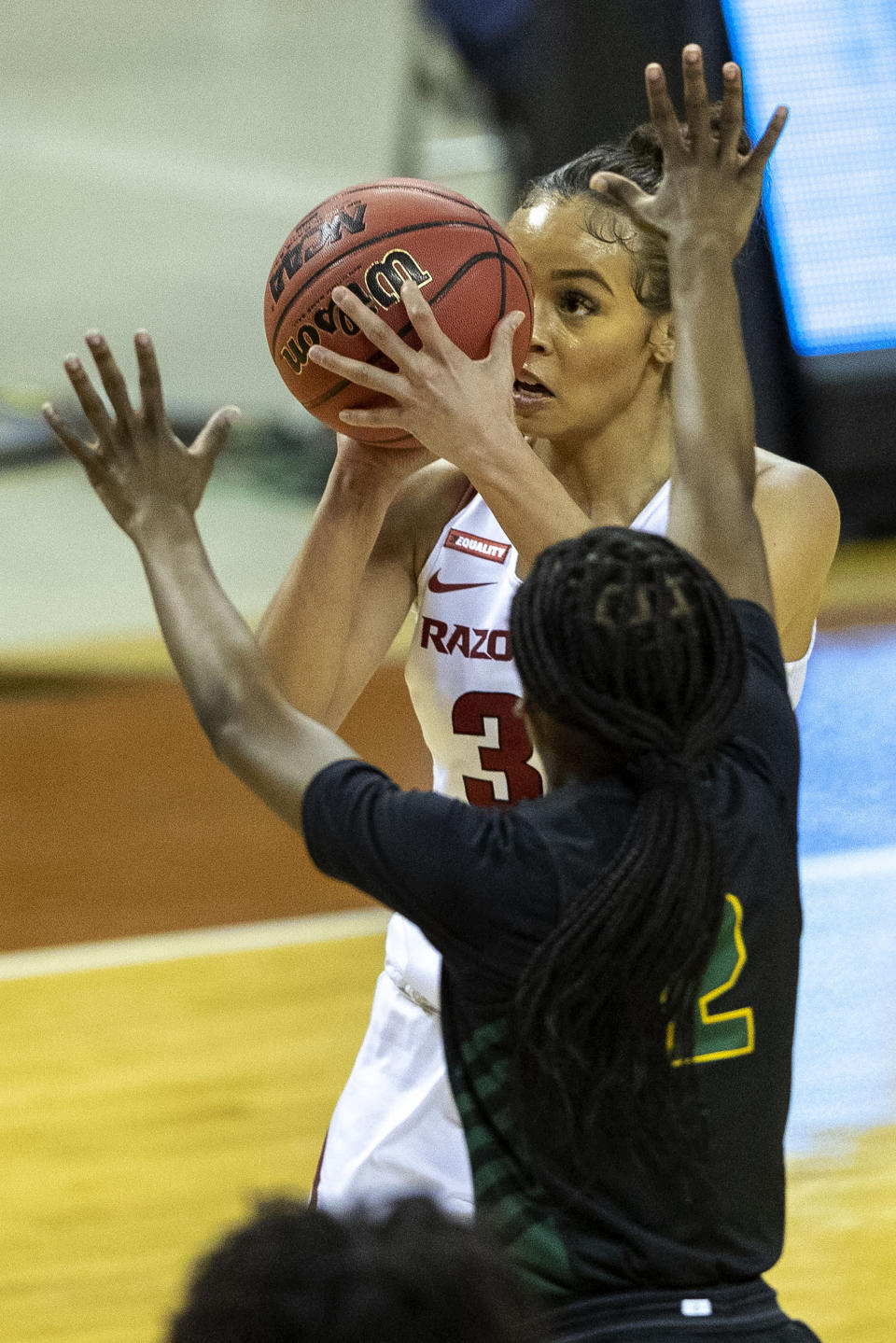 Arkansas guard Chelsea Dungee, left, shoots over Wright State guard Destyne Jackson during the first half of a college basketball game in the first round of the women's NCAA tournament at the Frank Erwin Center in Austin, Texas, Monday, March 22, 2021. (AP Photo/Stephen Spillman)