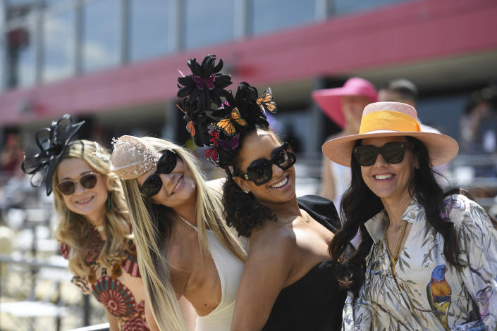 Women pose for a photograph ahead of the Preakness Stakes horse race at Pimlico Race Course, Saturday, May 15, 2021, in Baltimore. (AP Photo/Will Newton)