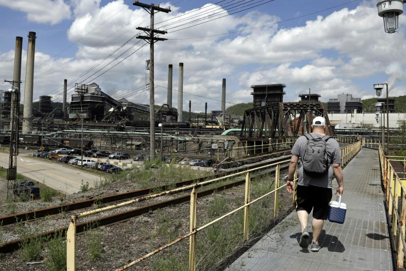 FILE - In this May 2, 2019, file photo a worker arrives for his shift at the U.S. Steel Clairton Coke Works in Clairton, Pa. A fire at U.S. Steel's massive coke plant outside Pittsburgh knocked a key pollution control system offline Monday, June 17, 2019. It triggered a health warning as officials monitored the air around the plant for signs of a release of toxic sulfur dioxide. It was the second fire since December at the coke works, the largest facility of its kind in the United States. The plant turns coal into coke, one of the raw materials of steel. (AP Photo/Gene J. Puskar, FILE)