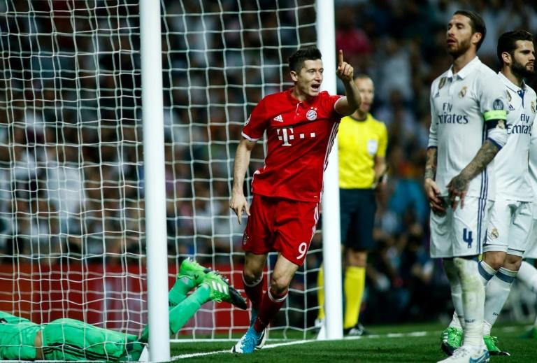 Bayern Munich's forward Robert Lewandowski (C) celebrates an own goal by Real Madrid's defender Sergio Ramos (2R) during the UEFA Champions League quarter-final second leg football match Real Madrid vs FC Bayern Munich