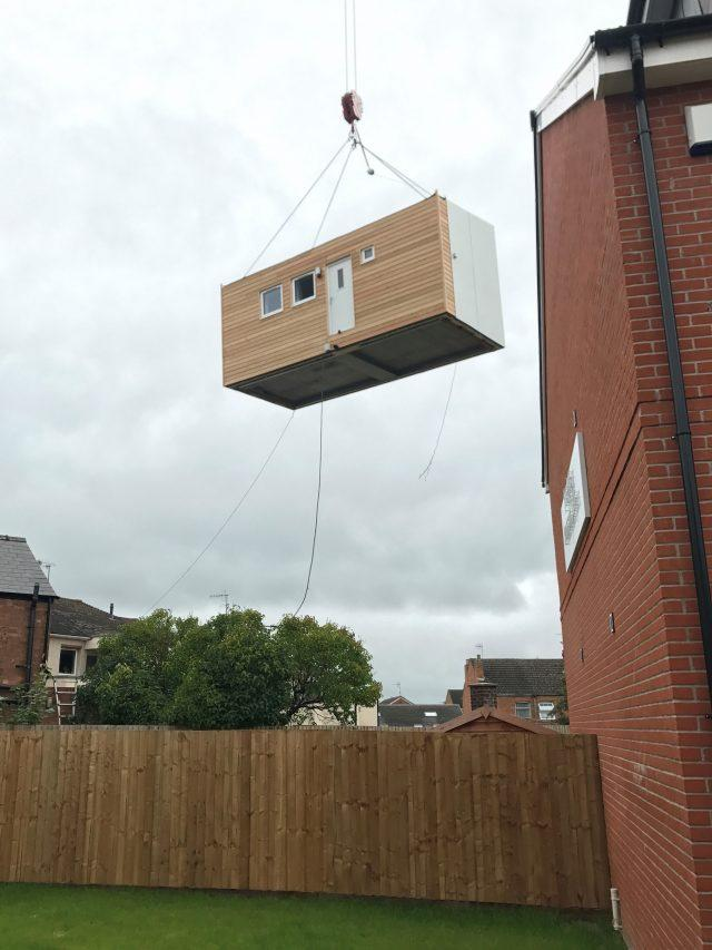 A micro-home is lifted into place