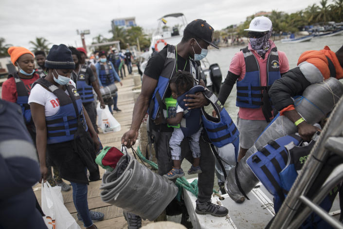 Migrants board a boat that will take them to Capurgana, on the border with Panama, from Necocli, Colombia, Thursday, July 29, 2021. Migrants have been gathering in Necocli as they move north towards Panama on their way to the U.S. border. (AP Photo/Ivan Valencia)