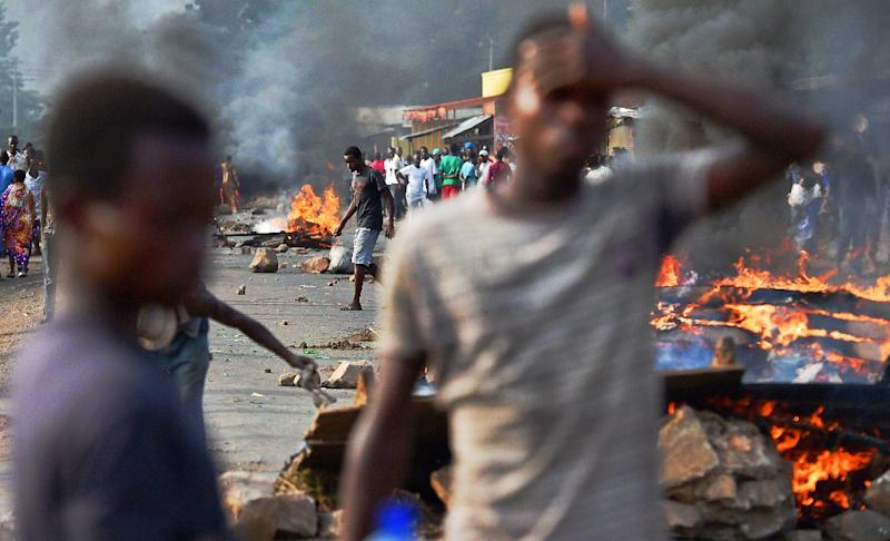 Protesters stands near a burning barricade during a demonstration against the Burundian President's third term candidature, in Bujumbura in May 2015