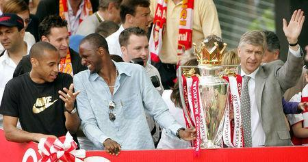 "FILE PHOTO: Arsenal's Thierry Henry, Patrick Viera and manager Arsene Wenger celebrate during a victory parade in north London May 16, 2004. Arsenal are celebrating their victory in the English premier league. Arsenal became the first team since Preston North End's ""Old Invincibles"" in the Football League's inaugural 1888-89 season to remain unbeaten in the top flight. REUTERS/Peter Macdiarmid/File Photo"
