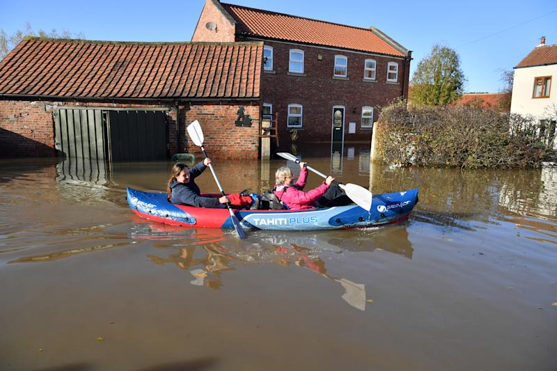 Two people canoeing through floodwater in Fishlake, Doncaster as parts of England endured a month's worth of rain in 24 hours, with scores of people rescued or forced to evacuate their homes. (Photo by Ben Birchall/PA Images via Getty Images)