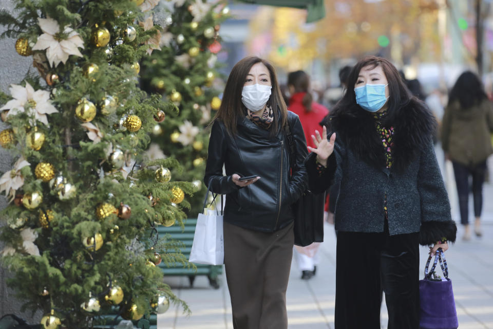 People wearing face masks to help curb the spread of the coronavirus walk at Ginza shopping district in Tokyo, Tuesday, Dec. 22, 2020. (AP Photo/Koji Sasahara)