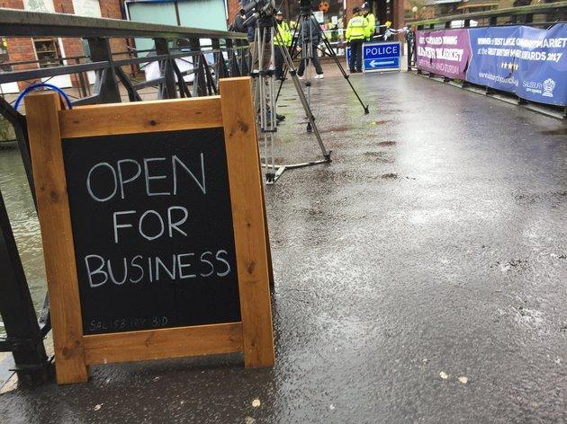 A sign reassures passersby the shops near the cordon are still open