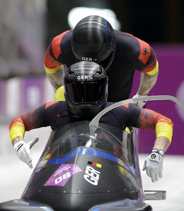 The team from Germany GER-2, piloted by Thomas Florschuetz and brakeman Kevin Kuske, start their third run during the men's two-man bobsled competition at the 2014 Winter Olympics, Monday, Feb. 17, 2014, in Krasnaya Polyana, Russia. (AP Photo/Michael Sohn)