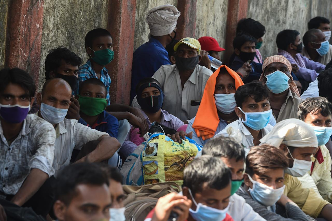 Migrant workers wait outside the Chhatrapati Shivaji Maharaj Terminus railway station before boarding trains to return to their homes after the government eased a nationwide lockdown as a preventive mearure against the COVID-19 coronavirus, in Mumbai on May 14, 2020. (Photo by Punit PARANJPE / AFP) (Photo by PUNIT PARANJPE/AFP via Getty Images)