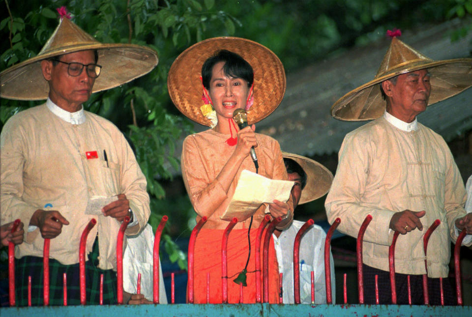 FILE - In this June 16, 1996 file photo, pro-democracy leader Aung San Suu Kyi, center, speaks to supporters outside her home in Rangoon, Myanmar, as senior leaders in the National League for Democracy Tin Oo, left, and U Kyi Maung listen. Myanmar's military has taken control of the country under a one-year state of emergency and reports say State Counsellor Aung San Suu Kyi and other government leaders have been detained. (AP Photo/Stuart Isett, File)