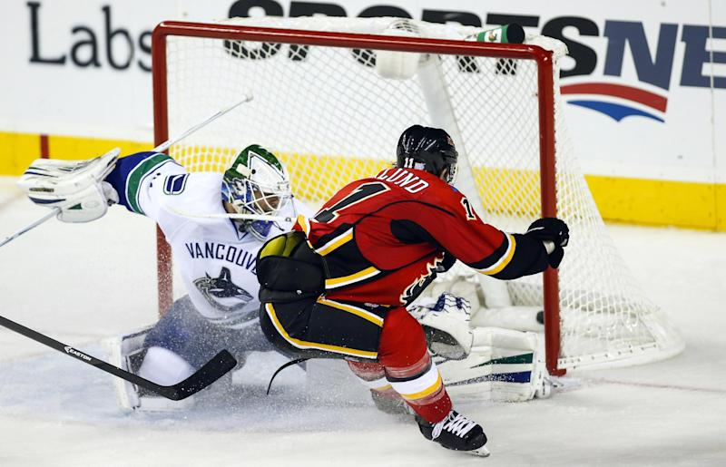 Vancouver Canucks goalie Eddie Lack, from Sweden, left, lets in a goal by Calgary Flames' Mikael Backlund, from Sweden, during second period NHL hockey action in Calgary, Alberta, Sunday, Oct. 6, 2013. (AP Photo/The Canadian Press, Jeff McIntosh)