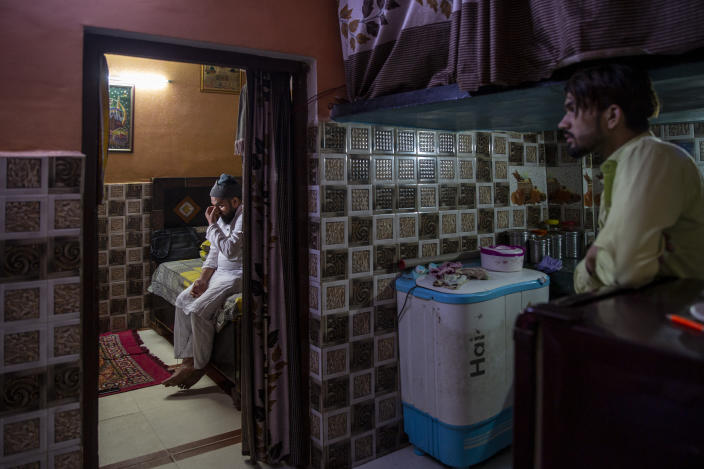 Haroon, left, who saw his 32 year-old brother being shot and killed by his Hindu neighbors during the February 2020 communal riots, breaks down while speaking to the Associated Press inside his home in North Ghonda, one of the worst riot affected neighborhood, in New Delhi, India, Friday, Feb. 19, 2021. As the first anniversary of bloody communal riots that convulsed the Indian capital approaches, Muslim victims are still shaken and struggling to make sense of their struggle to seek justice. (AP Photo/Altaf Qadri)