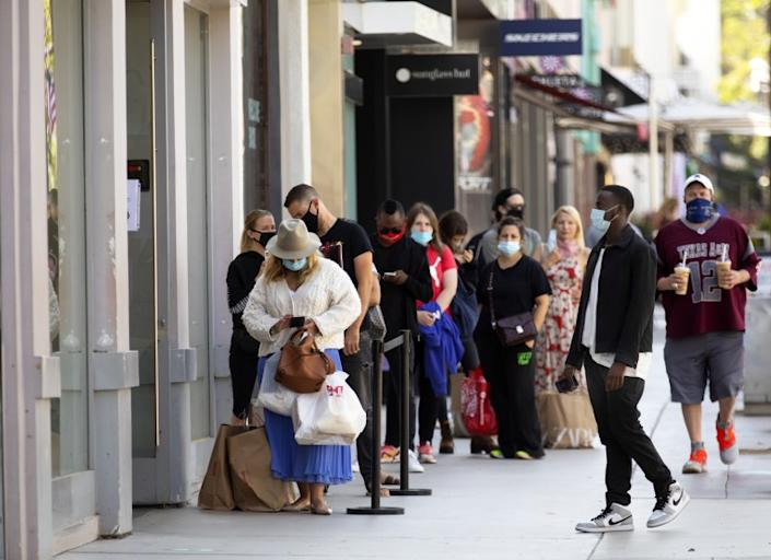 "Customers wearing masks line up to go inside Zara on the 3rd Street Promenade in Santa Monica. <span class=""copyright"">(Francine Orr / Los Angeles Times)</span>"