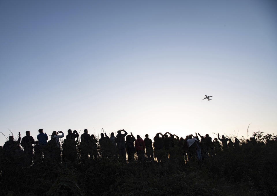 Hundreds of people watch and photograph the Airbus of the French airline Air France taking off from Tegel (TXL) airport in Berlin, Germany, Sunday, Nov. 8, 2020. Tegel Airport closes with the departure of the last scheduled flight number AF 1235 to Paris. (Paul Zinken/dpa via AP)