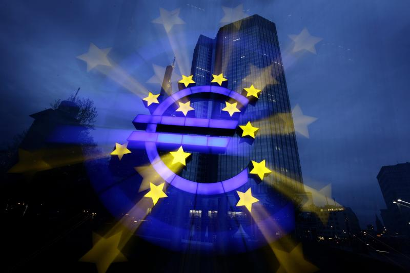 A zoom-burst image shows the illuminated euro sign in front of the headquarters of the European Central Bank (ECB) in Frankfurt