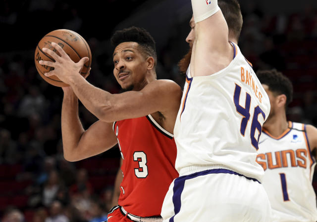 Portland Trail Blazers guard CJ McCollum, left, passes the ball on Phoenix Suns center Aron Baynes, right, during the first quarter of an NBA basketball game in Portland, Ore., Tuesday, March 10, 2020. (AP Photo/Steve Dykes)
