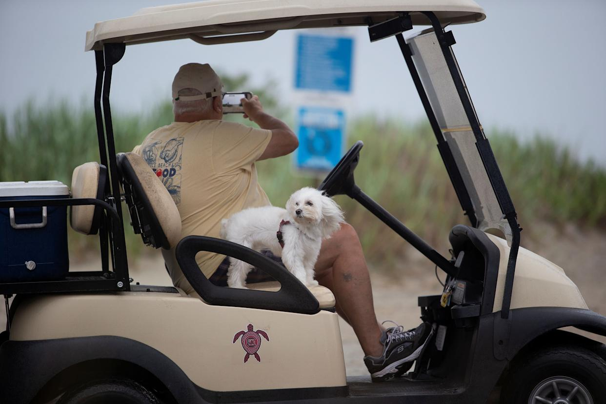 A man and his dog get a close look at the beach from a golf cart during Hurricane Florence in Surfside Beach, South Carolina, U.S. September 14, 2018.