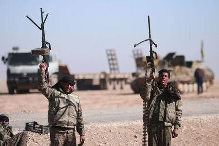 Syrian Democratic Forces fighters hold up their weapons in the north of Raqqa city, Syria. REUTERS/Rodi Said