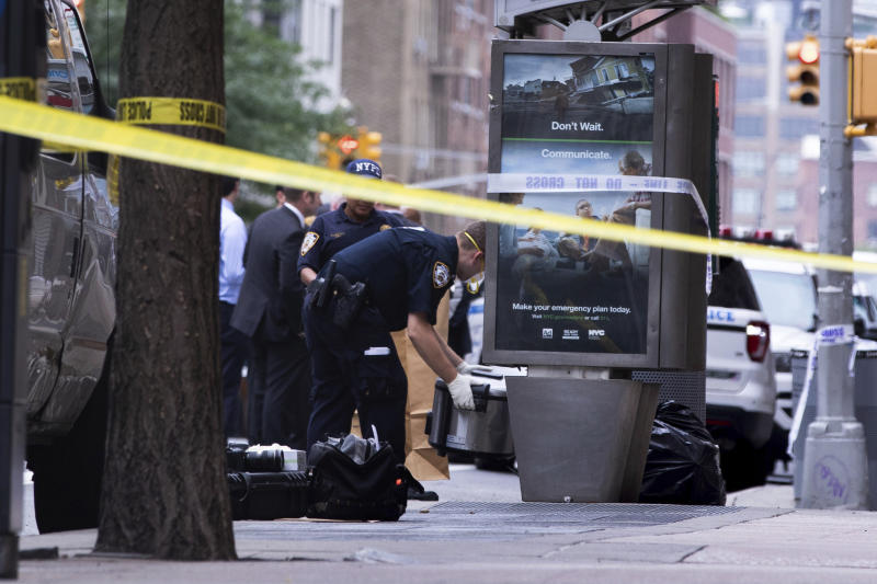 An investigator picks up a suspicious package that was thought to be an explosive device in Manhattan's Chelsea neighborhood Friday, Aug. 16, 2019, in New York.  The appliance was deemed harmless and taken away as evidence. (AP Photo/Kevin Hagen).