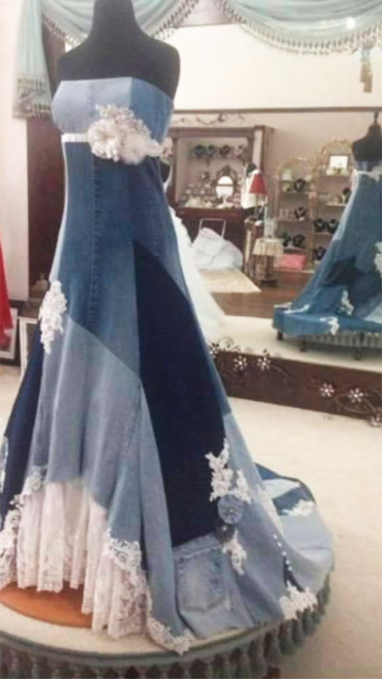 A gown in several shades of patched denim decorated with a lace hem, tulle flowers and lace and rhinestone sits on a mannequin in front of a large mirror.