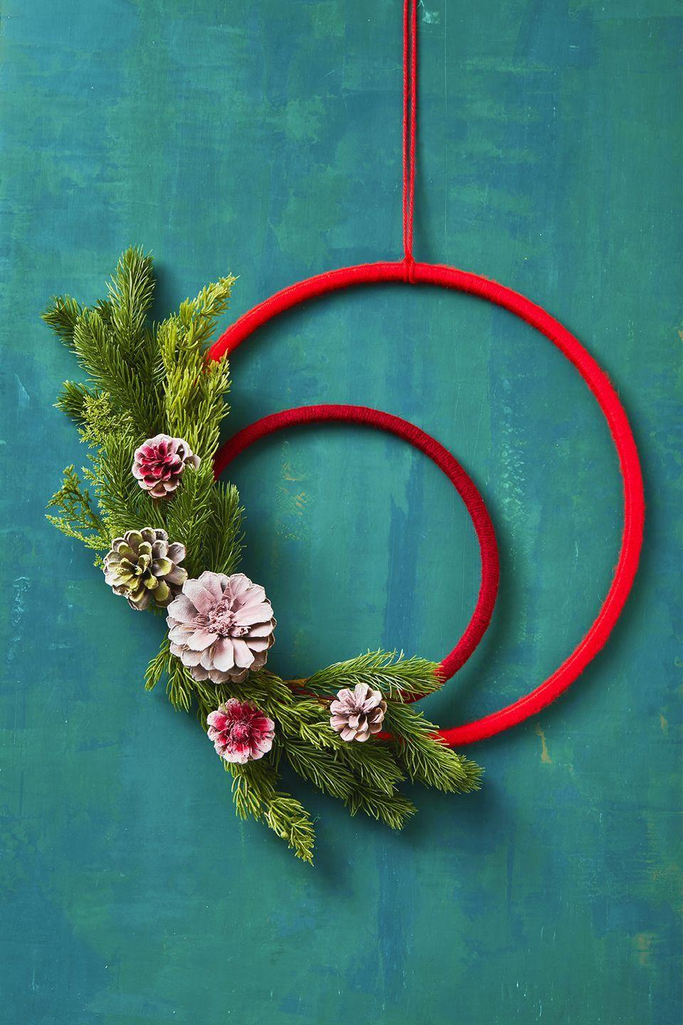 "<p>Wrap two embroidery hoops — one small, one large — with different shades of red thread, and then finish it off with fresh or faux pine branches and a medley of hand-painted pinecones. </p><p><strong>RELATED: </strong><a href=""https://www.goodhousekeeping.com/home/craft-ideas/how-to/g1488/diy-winter-wreaths/"" rel=""nofollow noopener"" target=""_blank"" data-ylk=""slk:Winter Wreaths That You Can DIY"" class=""link rapid-noclick-resp"">Winter Wreaths That You Can DIY </a></p>"