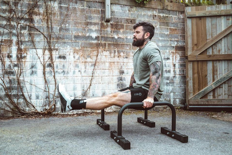 """<p>Have you ever seen a gymnast without a six-pack? Exactly. But you don't <em>have</em> to be reeling off <a href=""""https://www.menshealth.com/uk/adventure/a32019309/muscle-up/"""" rel=""""nofollow noopener"""" target=""""_blank"""" data-ylk=""""slk:ring muscle-ups"""" class=""""link rapid-noclick-resp"""">ring muscle-ups</a> in order to harness their enviable core definition and control. </p><p>This home workout, devised by <a href=""""https://www.instagram.com/scottbrits/"""" rel=""""nofollow noopener"""" target=""""_blank"""" data-ylk=""""slk:Scott Britton"""" class=""""link rapid-noclick-resp"""">Scott Britton</a>, founder of <a href=""""https://www.instagram.com/battle.cancer/"""" rel=""""nofollow noopener"""" target=""""_blank"""" data-ylk=""""slk:Battle Cancer"""" class=""""link rapid-noclick-resp"""">Battle Cancer</a>, starts with the L-Sit: holding your legs straight in front of you with your arms locked out, as if in the top position of a dip. More clearance from the floor makes this infinitely easier to achieve, thankfully. Parallettes, <a href=""""https://www.argos.co.uk/product/6189657"""" rel=""""nofollow noopener"""" target=""""_blank"""" data-ylk=""""slk:like these"""" class=""""link rapid-noclick-resp"""">like these</a>, are ideal but the seats of two solid chairs or boxes is just as good. </p><p>Start with a 10-second hold. After each L-Sit, you've got 15 reps of dips and hand-elevated pushups, to ensure your arms and chest get good pump while you're core takes a break. Add two seconds to the L-sit each round and keep going until you reach 10 rounds in total. The holds will get tough, so if you hit a wall on them, simply aim for the maximum time in the L-Sit each round. </p><p>You'll become much stronger in the position after only a couple of sessions, so give yourself a day off and then fit the session in again. With the Olympics pushed back until 2021, you still have plenty of time to make the US gymnastics squad...</p>"""
