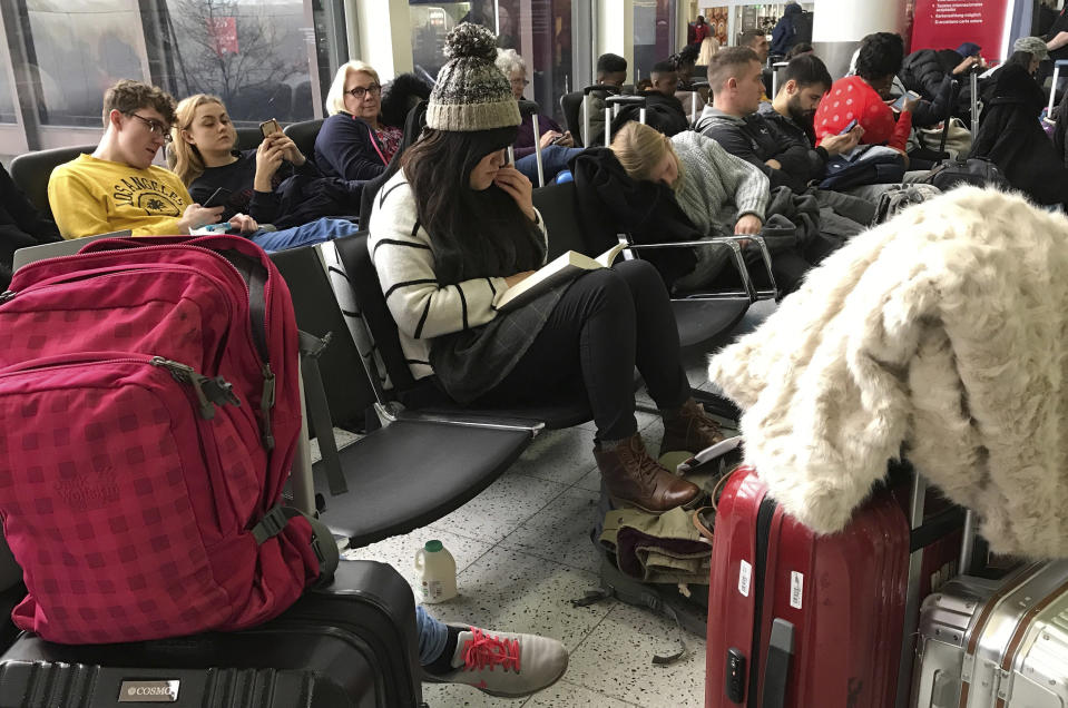 Passengers wait at Gatwick Airport in England, Friday, Dec. 21, 2018. Flights resumed at London's Gatwick Airport on Friday morning after drones sparked the shutdown of the airfield for more than 24 hours, leaving tens of thousands of passengers stranded or delayed during the busy holiday season.(AP Photo/Kirsty Wigglesworth)