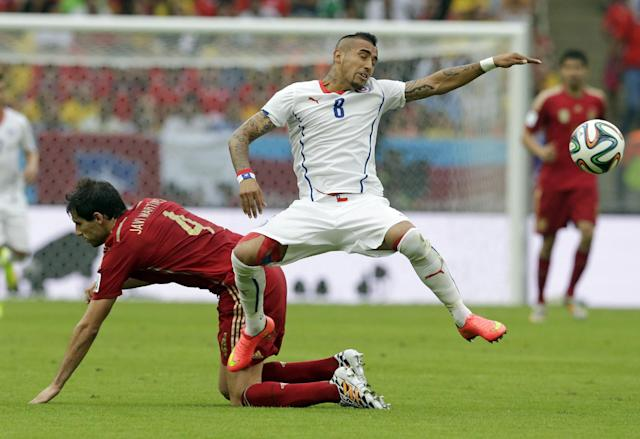 Chile's Arturo Vidal, right, is challenged by Spain's Javi Martinez during the group B World Cup soccer match between Spain and Chile at the Maracana Stadium in Rio de Janeiro, Brazil, Wednesday, June 18, 2014