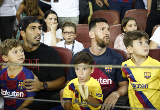 Barcelona's Lionel Messi, right, and Barcelona's Luis Suarez sit in the stands prior of the Spanish La Liga soccer match between FC Barcelona and Betis at the Camp Nou stadium in Barcelona, Spain, Sunday, Aug. 25, 2019. (AP Photo/Joan Monfort)