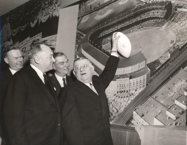 FILE - In this Jan. 27, 1956, file photo, NFL commissioner Bert Bell, right, gestures towards a mural of Yankee Stadium while talking with Wellington Mara, rear left, then-New York Giants secretary, his brother Jack Mara, rear right, Giants' president, and George Weiss, Yankees general manager, front left, in New York. Bert Bell was not the first NFL commissioner. He was, however, the first to make a major impact on pro football. To call Bell the father of the NFL draft would be accurate. It also would be an incomplete assessment, because Bell was a brilliant innovator who helped carry his league from afterthought to a player among American sports. (AP Photo/File)