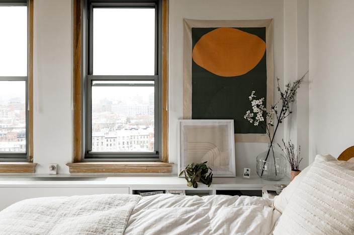 """<div class=""""caption""""> """"A long time ago, a mentor of mine told me a bedroom should be just for sleep,"""" says the actress, who kept things feeling calm with white bedding and a cotton canvas print from <a href=""""https://www.whatsupton.com/"""" rel=""""nofollow noopener"""" target=""""_blank"""" data-ylk=""""slk:Upton"""" class=""""link rapid-noclick-resp"""">Upton</a>. """"I let the windows be the focus here, above all."""" </div>"""