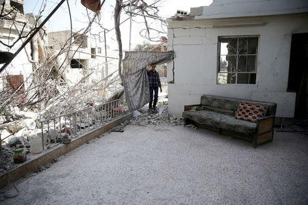 A boy inspects a damaged house in the rebel-held besieged city of Douma, a suburb of Damascus