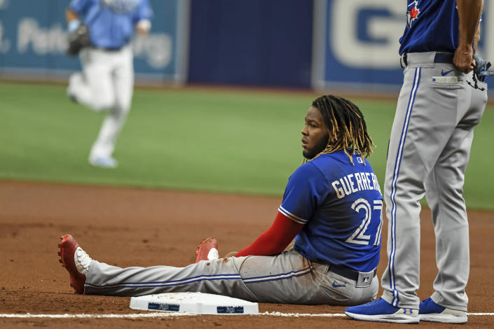 Toronto Blue Jays' Vladimir Guerrero Jr. sits in the dirt after he was picked off first base on a throw from Tampa Bay Rays catcher Mike Zunino during the first inning of a baseball game Saturday, July 10, 2021, in St. Petersburg, Fla. (AP Photo/Steve Nesius)