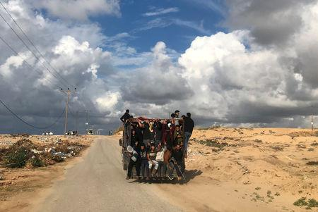 FILE PHOTO: Palestinians ride a truck on their way to a protest calling for lifting the Israeli blockade on Gaza, near the beachfront border with Israel, in the northern Gaza Strip November 5, 2018. REUTERS/Mohammed Salem/File Photo