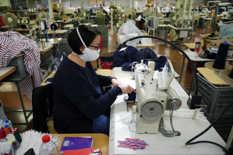 In this Friday, June 12, 2020 photo, an employee sews face protective masks in Chanteclair Hosiery, a French knitwear clothing manufacturer in Saint Pouange, east of Paris. The French praised the altruism of luxury goods companies such as LVMH, Kering and Chanel, for altruism for diverting their production facilities to make millions of face masks for the public during the peak of their country's coronavirus outbreak. Now, the companies that helped France avoid a dangerous shortage say they need help unloading a surplus of 20 million washable masks. (AP Photo/Francois Mori)
