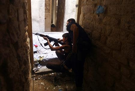Ahmad Abu Layl, a 15 year-old fighter from the Free Syrian Army, aims his weapon as his father stands behind him in Aleppo September 10, 2013. REUTERS/Hamid Khatib