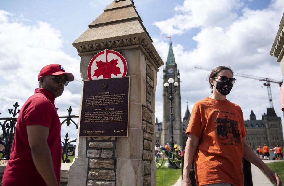 """<span class=""""caption"""">An upside down maple leaf is tucked behind a plaque as people gather on Parliament Hill in Ottawa at a rally to honour the lives lost to residential schools and demand justice for Indigenous peoples, on Canada Day, July 1, 2021. </span> <span class=""""attribution""""><span class=""""source"""">THE CANADIAN PRESS/Justin Tang </span></span>"""