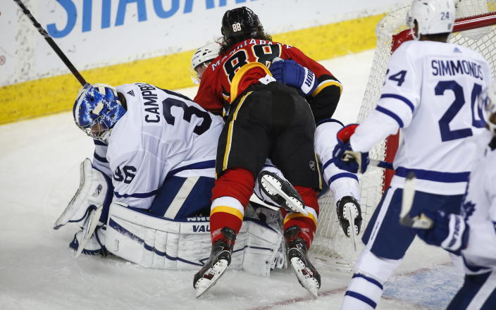 Toronto Maple Leafs goalie Jack Campbell, left, hangs onto the puck as Calgary Flames' Andrew Mangiapane crashes over him during third-period NHL hockey game action in Calgary, Alberta, Sunday, Jan. 24, 2021. (Jeff McIntosh/The Canadian Press via AP)