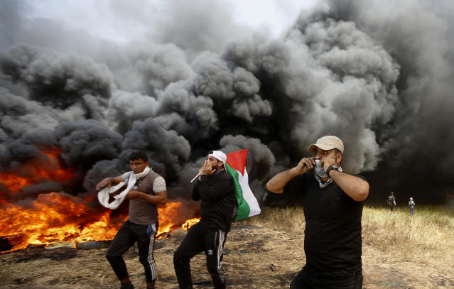 <p>Palestinian protesters chant slogans next to burning tires during clashes with Israeli troops along Gaza's border with Israel, east of Khan Younis, Gaza Strip, Friday, April 6, 2018. (Photo: Adel Hana/AP) </p>