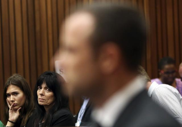 An unidentified family friend of the Steenkamp family glances at Olympic and Paralympic track star Oscar Pistorius during the fifth day of his trial for the murder of his girlfriend Reeva Steenkamp at the North Gauteng High Court in Pretoria, March 7, 2014. REUTERS/Themba Hadebe/Pool (SOUTH AFRICA - Tags: SPORT ATHLETICS CRIME LAW)