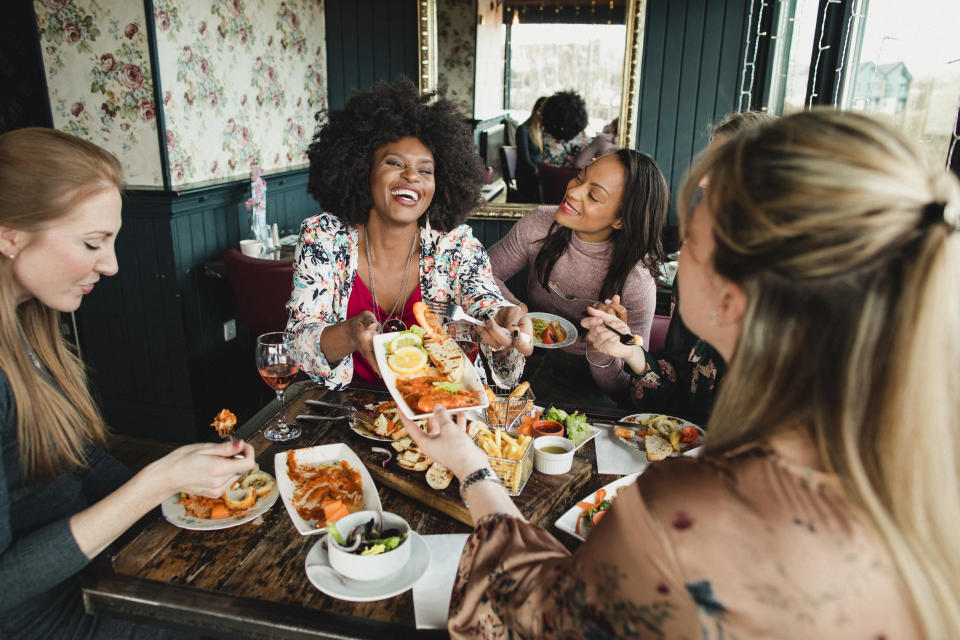 A group of women are enjoying a meal in a restaurant with rose wine. They have a king prawns sharing platter , one woman can be seen passing her friend a plate of food. Mixed ethnic group