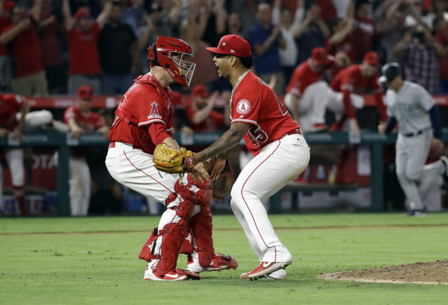 Los Angeles Angels relief pitcher Felix Pena, right, celebrates with catcher Dustin Garneau after the Angels threw a combined no-hitter against the Seattle Mariners during a baseball game Friday, July 12, 2019, in Anaheim, Calif. Taylor Cole pitched the first two innings. (AP Photo/Marcio Jose Sanchez)