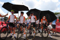 Annemiek van Vleuten, from left, Anna van der Breggen, Demi Vollering and Marianne Vos of the Netherlands protect from the sun with an umbrella before they compete in the women's cycling road race at the 2020 Summer Olympics, Sunday, July 25, 2021, in Oyama, Japan. (Michael Steele/Pool Photo via AP)
