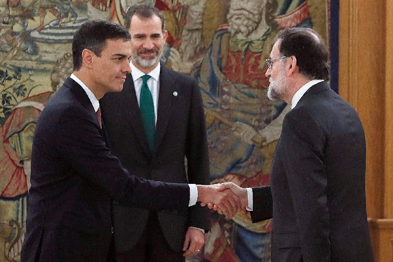 Spain's new Prime Minister Pedro Sanchez (l) shakes hands with predecessor Mariano Rajoy in front of Spain's King Felipe VI during the swearing-in ceremony (AFP Photo/Fernando Alvarado)